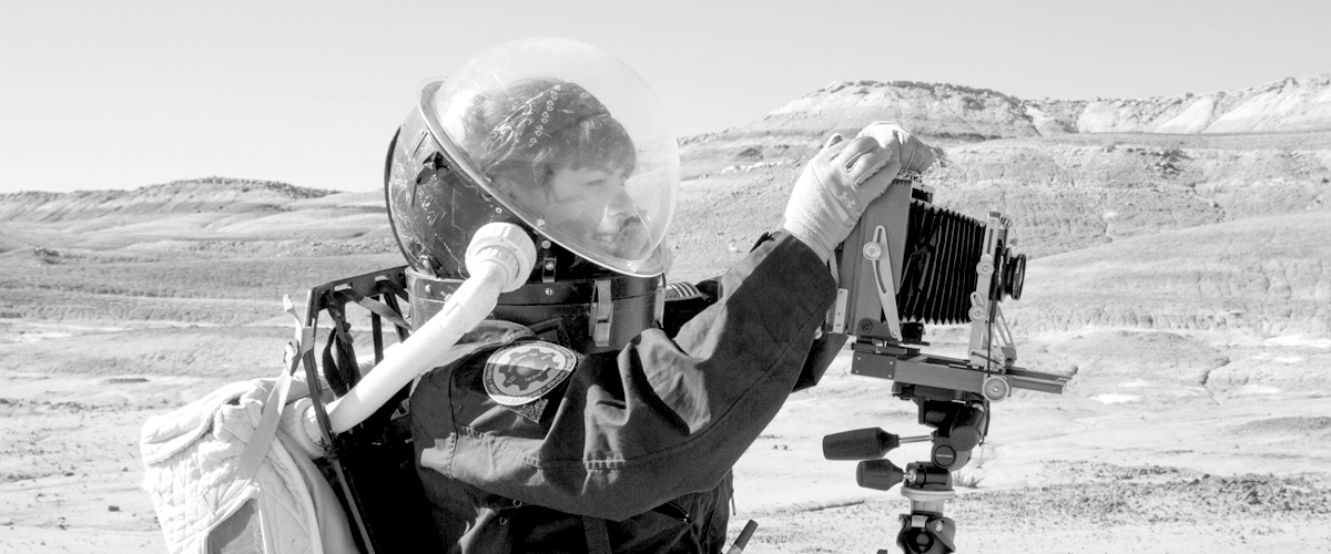 A woman in a space suit with a film camera