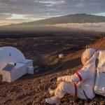 A person in a spacesuit sitting on a hill in what looks like Mars