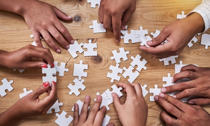 Hands putting together a puzzle