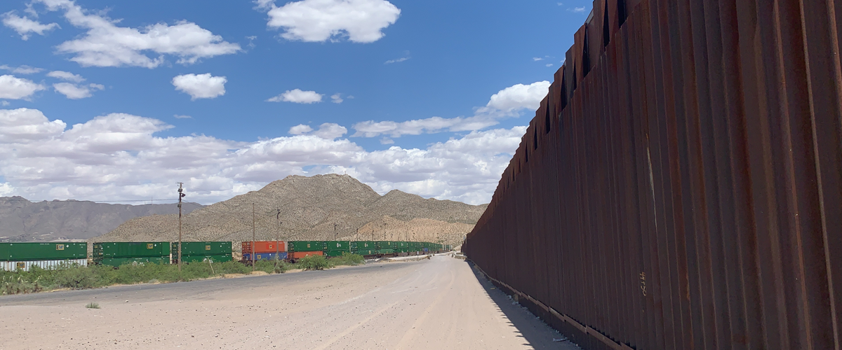border fence and trains in the distance