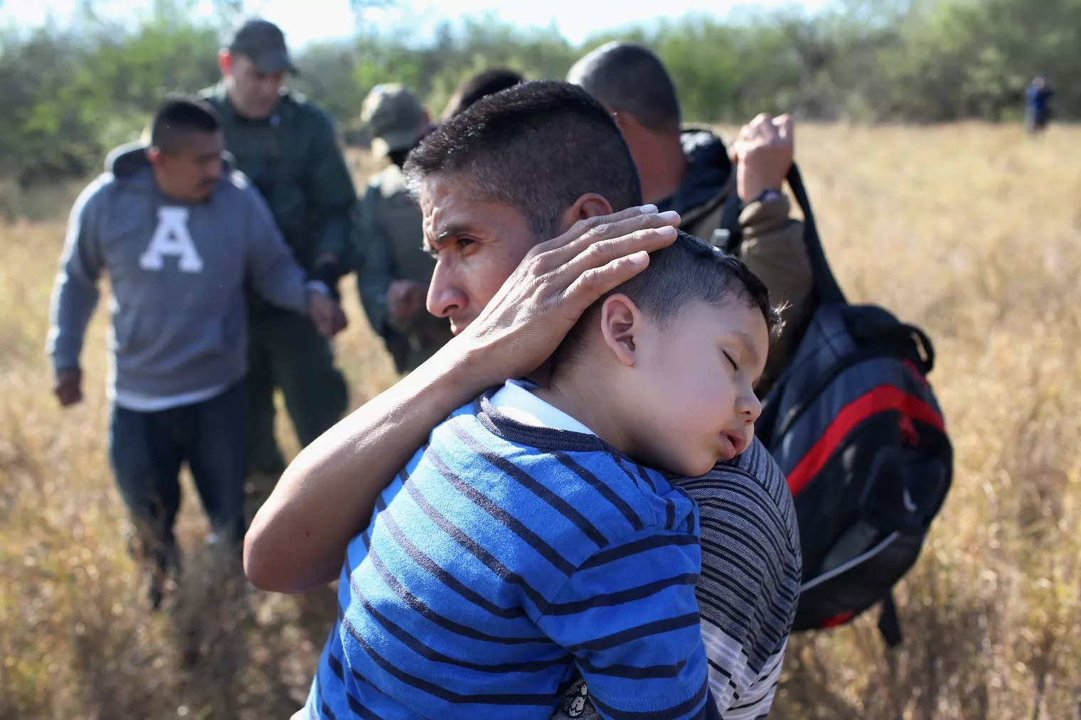 A migrant father hugging his son near the US-Mexico border